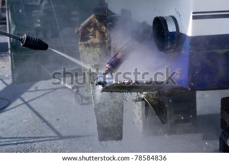 blue boat hull cleaning pressure washer barnacles antifouling and seaweed - stock photo
