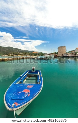 Blue boat in the harbor in the seaside resort on summer day