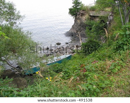 blue boat on the edge of Lake Champlaigne - stock photo