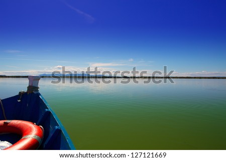 Blue boat sailing in Albufera lake of Valencia in a sunny blue sky day