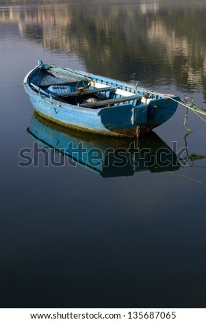 Blue boat . Small fishing boat moored in calm water at Ribadesella, Asturias, North Spain, Europe. - stock photo