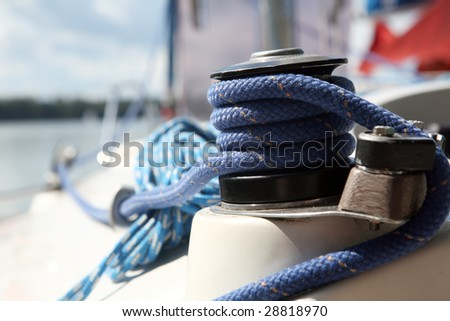 blue boater's rope on belaying cleat, yacht equipment - stock photo