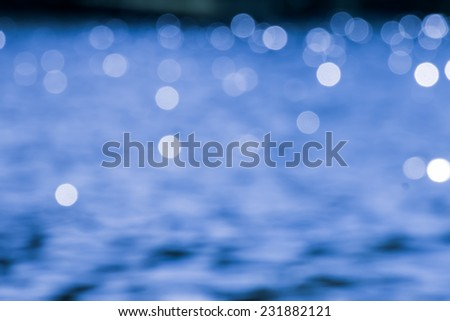 Blue bokeh on the water in black background - stock photo