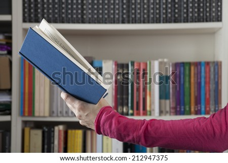 blue book in pink woman arm over library background - stock photo