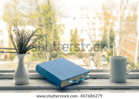 Blue book with bookmarks, a vase and a cup. View from the window.  - stock photo