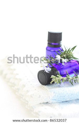 Blue bottle aroma oil with rosemary and towel