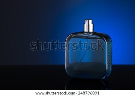 Blue bottle of perfume  isolated on blue background - stock photo