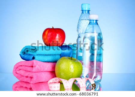 Blue bottle of water, apple, sports towel and measure tape on blue background - stock photo