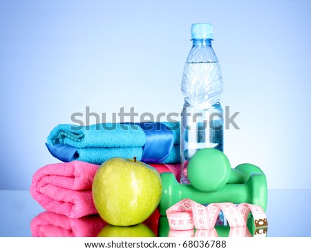 Blue bottle of water, apple, sports towel, measure tape and dumbbells on blue background