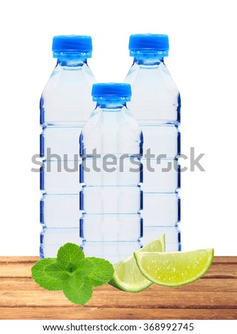 Blue bottles with water, mint herb and lime slices on table isolated on white background - stock photo