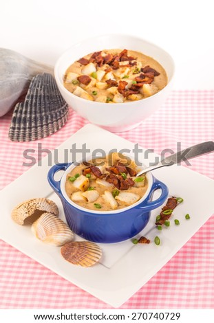 Blue bowl of sea scallop bisque in foreground with larger serving bowl against white background.   Surrounded by seashells on Pink Gingham Tablecloth in vertical format. - stock photo