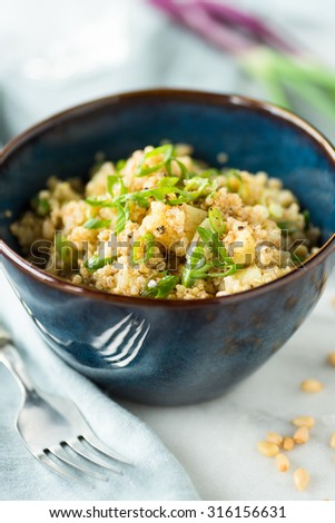 Blue bowl of spiced quinoa salad with potatoes - stock photo