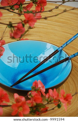 Blue bowl with chopstick and japanese cherry tree branches - stock photo