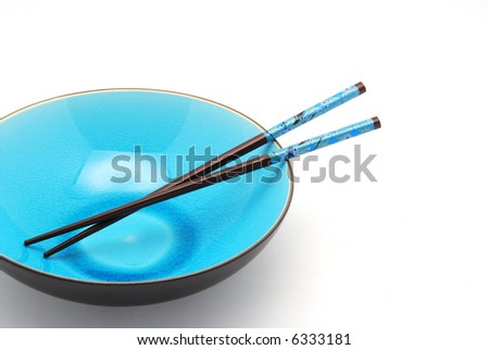 Blue bowl with chopsticks over white - stock photo