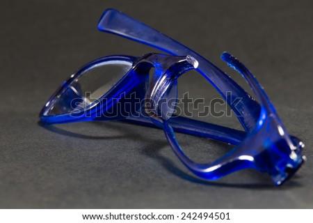 blue broken glasses on black background - stock photo
