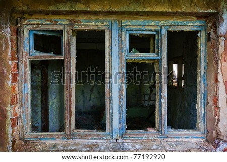 blue broken window in the abandoned old house - stock photo