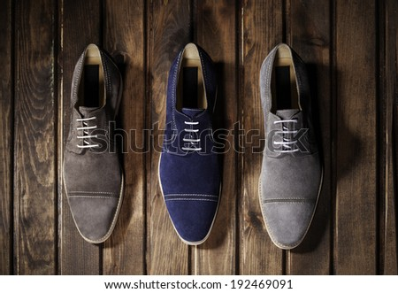 Blue, Brown and Gray Suede Shoes on a Wooden Background. - stock photo