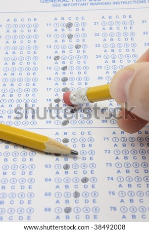 Blue, bubble test form completed for an exam  with a man erasing the answer circle with a number 2 pencil. - stock photo