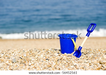 Blue Bucket And Spade Lying On A Beach - stock photo
