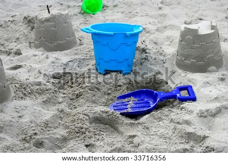Blue bucket and spade on the sand with constructed sandcastles and green bucket in the background - stock photo