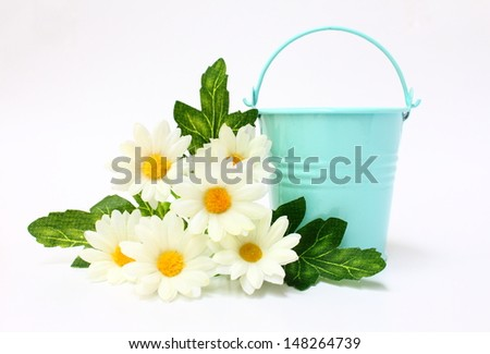 Blue bucket decorated with white flowers and leaves on white background