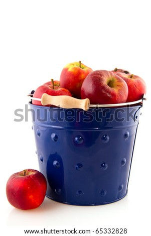 Blue bucket filled with red apples isolated over white