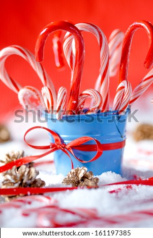 Blue bucket full of peppermint canes covered with snow - stock photo