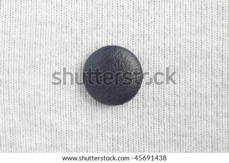 Blue button at the center on white cloth - stock photo