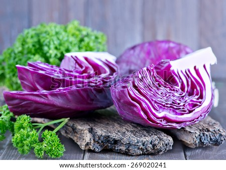 blue cabbage on board and on a table - stock photo