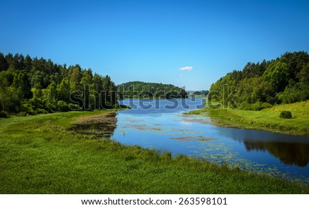 blue calm river in the forests and fields - stock photo