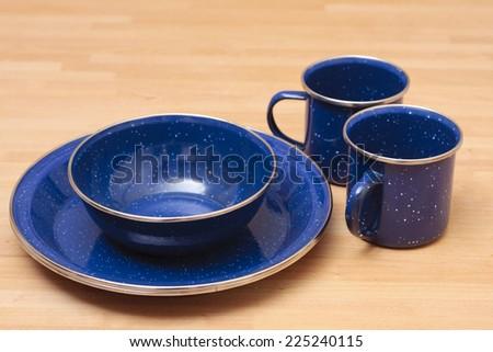 Blue camping enamel plates, bowls and mugs - stock photo