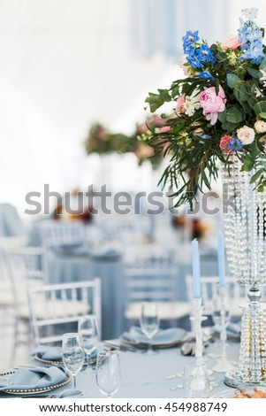Blue canldes and glassware surround high vase with pretty bouquet - stock photo