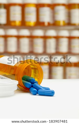 Blue capsules spilling from prescription medicine bottle on a white counter with rows of medicine bottles in a medicine cabinet in the background. Focus on opening of bottle and foreground copy space. - stock photo