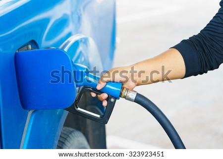blue car and blue Fuel nozzle on a gas station - stock photo