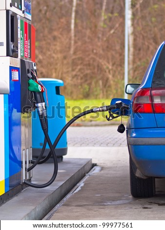 Blue car at gas station being filled with fuel against inflated prices - stock photo