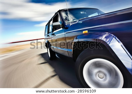 Blue Car in motion with deep blue sky - stock photo