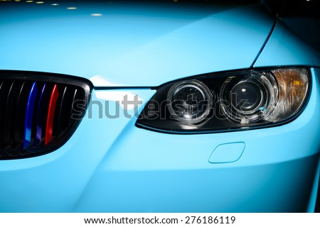 Blue car with headlight, grille and bumper - stock photo