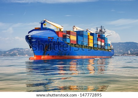 blue cargo container ship anchored in harbor - stock photo