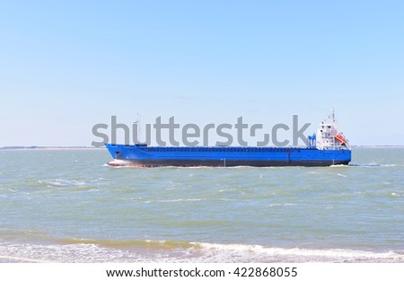 Blue cargo ship sailing to Antwerp port in the sea - stock photo