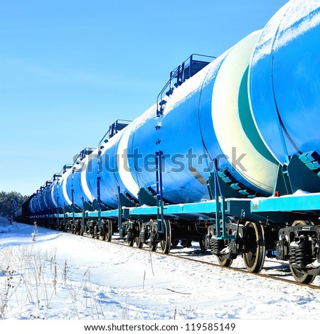 blue cargo train on the move in winter - stock photo