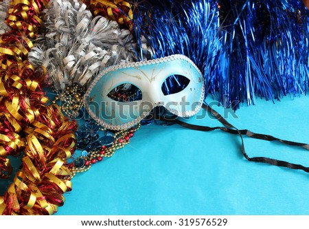 Blue carnival mask on a blue background with festive decorations - stock photo