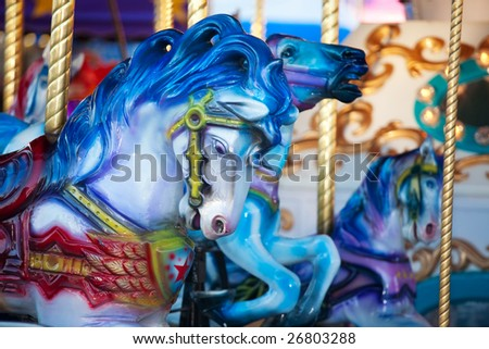 Blue carousal horses on a carnival merry-go-round. - stock photo