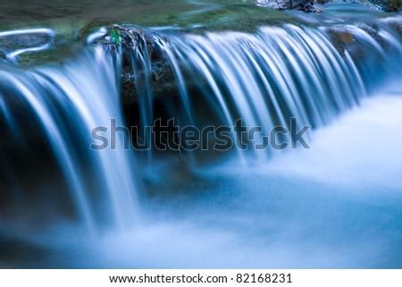 Blue cascade of mountain river - stock photo