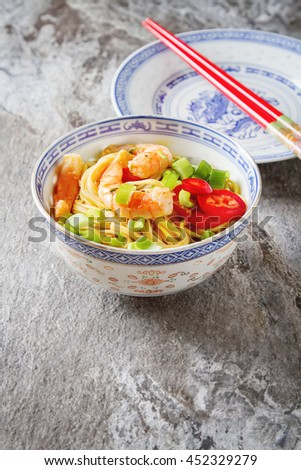 Blue ceramic cup noodles with vegetables, shrimps, green onions in sweet and sour Sauce. The red chopstikks on a gray stone background. Selective focus.  - stock photo