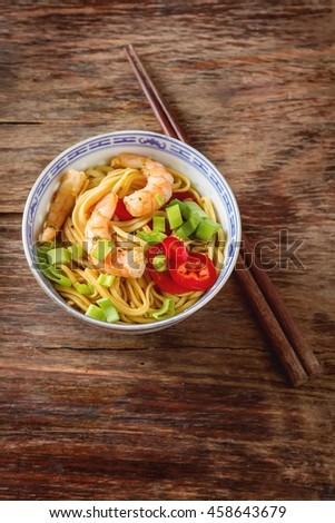 Blue ceramic cup noodles with vegetables, shrimps, green onions in sweet and sour Sauce with chopsticks on a dark wooden background. Selective focus.  - stock photo