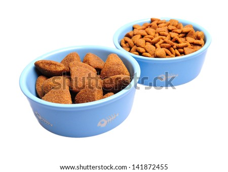 Blue ceramic dogs bowl. Dry dog food in bowl isolated on white background. - stock photo