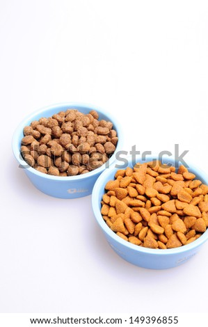 Blue ceramic dogs bowls. Dry dog food in bowl on white background. Dry dog food on white background - stock photo