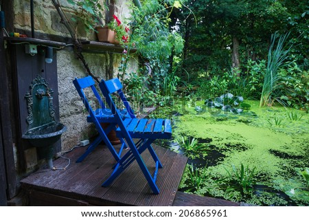 Blue chairs in front of a garden pond - stock photo
