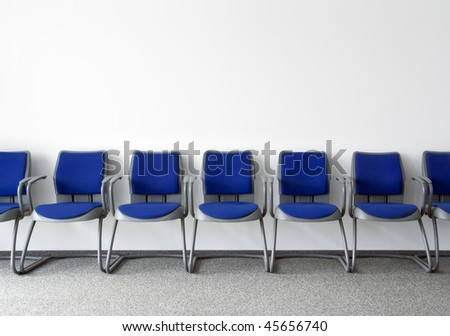 Blue chairs in ordinary empty waiting room - stock photo