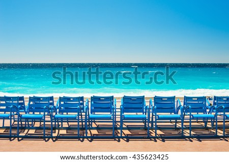 Blue chairs on the Promenade des Anglais in Nice, France. Beautiful turquoise sea and beach - stock photo